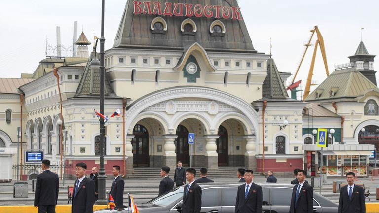Bodyguards surround the North Korean leader's limousine outside the railway station in Vladivostok