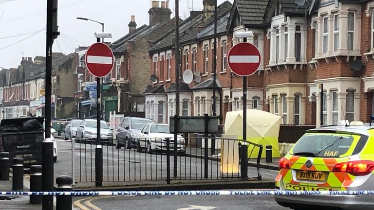 Police at the scene where a man in his 20s died of gunshot and stab wounds in east London