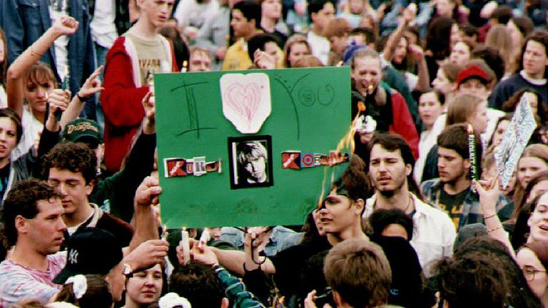 Fans of Cobain burn a poster bearing his photograph and reading 'I Love You' during a vigil in his memory, 10 April 1994 at the Seattle Center
