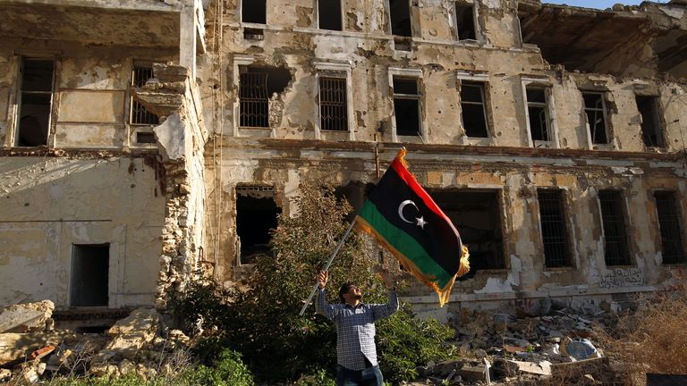 A Libyan man waves the national flag during a gathering to mark the eighth anniversary of the uprising in Libya's second city of Benghazi, on February 17, 2019. - Eight years after the revolt in Libya against Moamer Kadhafi's authoritarian regime, a modern and democratic state remains a distant dream in a country which has been sliding from crisis to crisis