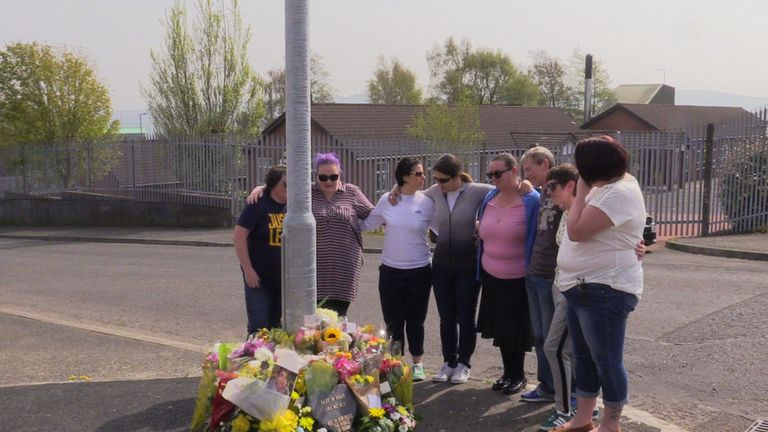A group of Ms McKee's friends gather at the site where she was shot