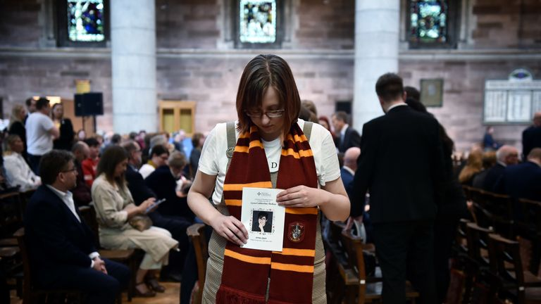A mourner wearing a Gryffindor scarf holds an order of service for Lyra McKee's funeral