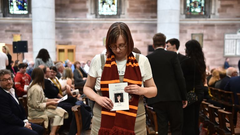 A mourner wearing a Hogwarts scarf holds the order of service for the funeral for journalist Lyra McKee at St Anne's Cathedral on April 24, 2019
