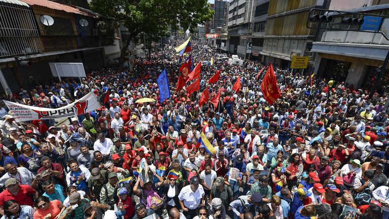 "Supporters of Venezuelan President Nicolas Maduro take part in a rally in the surroundings of Miraflores Presidential Palace in Caracas on April 30, 2019 after troops joined opposition leader Juan Guaido in his campaign to oust Maduro's government. - Guaido -- accused by the government of attempting a coup Tuesday -- said there was ""no turning back"" in his attempt to oust President Nicolas Maduro from power"