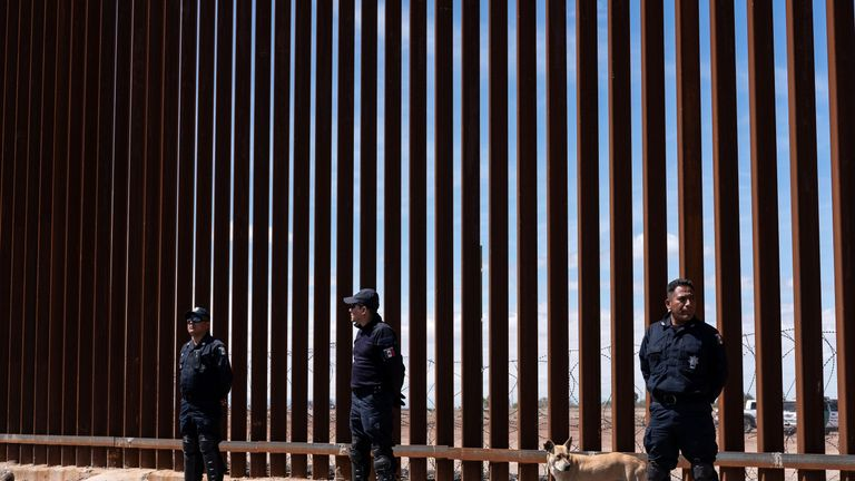 Mexican border police stand at the steel-slate fencing that separates the two countries
