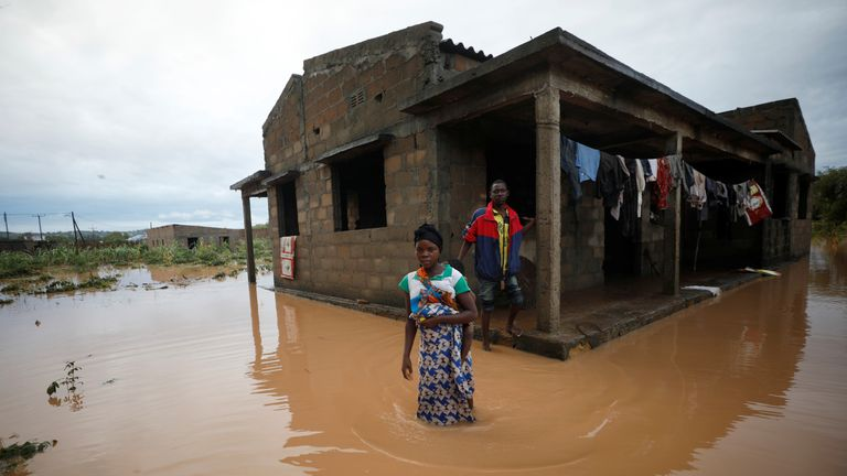 Agiro Cavanda and his wife Agera wade through floodwaters outside their home, flooded in the aftermath of Cyclone Kenneth, at Wimbe village in Pemba, Mozambique, April 29, 2019. REUTERS/Mike Hutchings