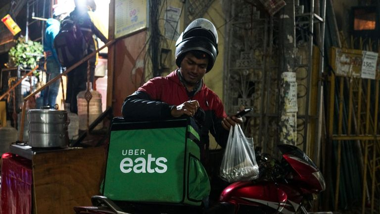 taken on February 6, 2019, an Indian delivery man working with the Uber Eats food delivery app loads up food to bring to a customer in New Delhi