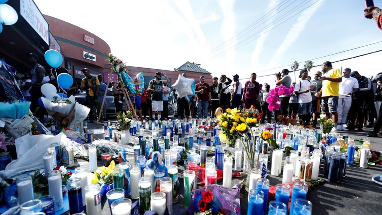 People gather around a makeshift memorial for Nipsey Hussle