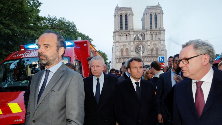 French Prime Minister Edouard Philippe, Minister of Culture Franck Riester and French President Emmanuel Macron gather near the Notre Dame Cathedral as its burns in Paris