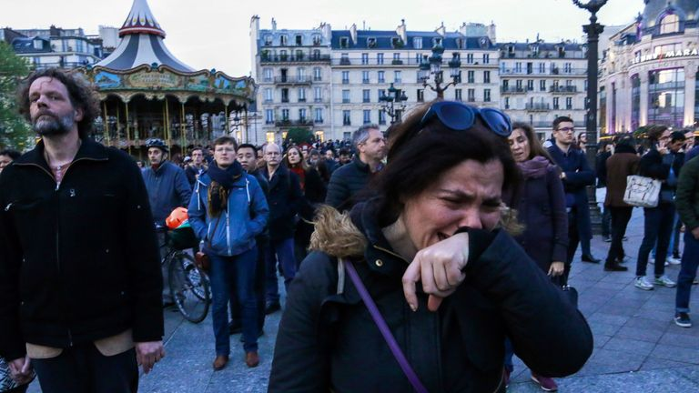 A woman cries as people look at Notre-Dame de Paris Cathedral engulfed in flames