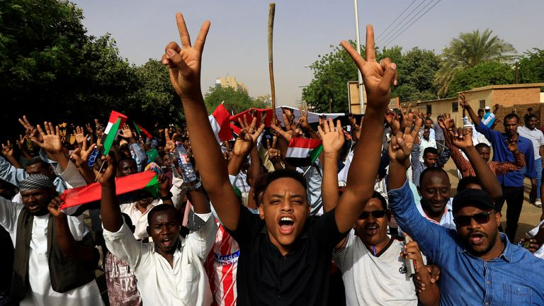 Sudanese demonstrators raise victory signs as president Omar al Bashir steps down