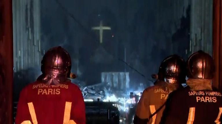 Firefights check over the cathedral after the fire is put out.