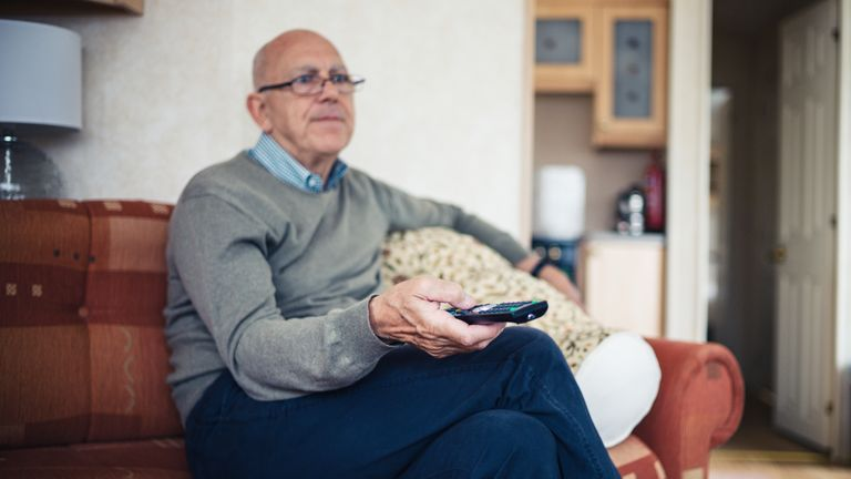 A senior man is sitting at home on a sofa and is watching television