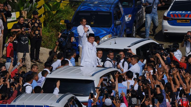 Presidential candidate Prabowo Subianto waves to a crowd after voting