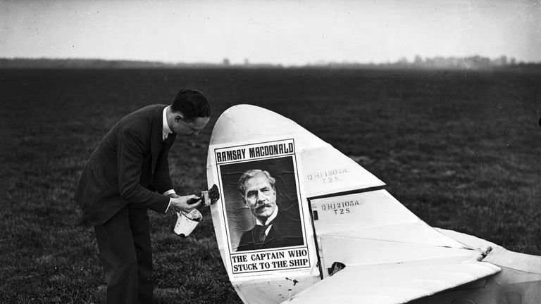 19th October 1931: Mr Mahony pastes an election poster for Labour politician Ramsay MacDonald (1866 - 1937) on the tail of his aeroplane at Heston airfield. (Photo by Fox Photos/Getty Images)