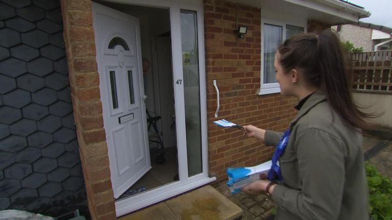 A Tory campaigner tries to deliver a leaflet to a pensioner
