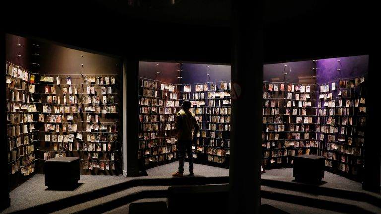 A visitor looks at an exhibition displaying pictures of victims at the Genocide Memorial in Gisoz