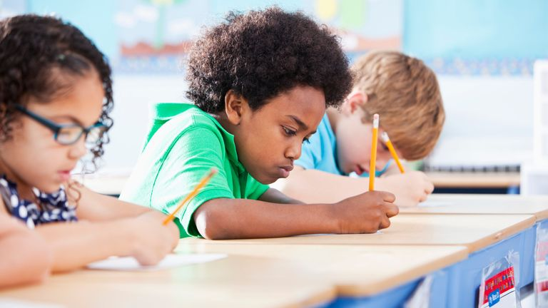 Elementary school children writing in class - Stock image