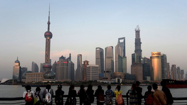 This photo taken on April 15, 2013 shows tourists watching the sunset over the Pudong financial district of Shanghai