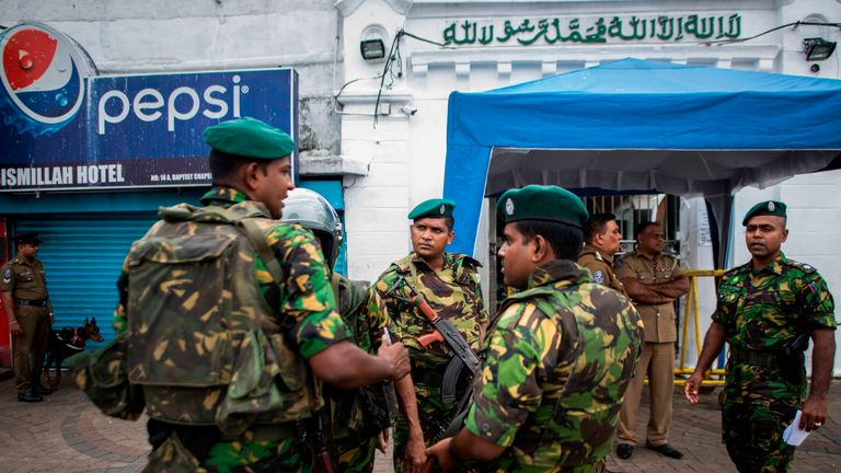 Armed soldiers stand guard outside a mosque during Friday prayers