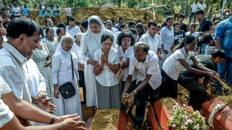Relatives of dead offer their prayers during funeral in Katuwapity village