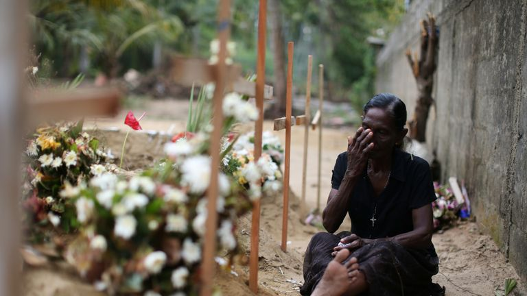 A woman sit by a grave after mass burials near St Sebastian church in Negombo