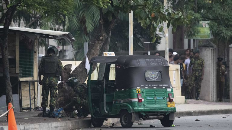 Soldiers search an abandoned vehicle in Sri Lanka's capital Colombo on Friday