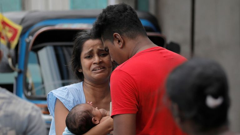 A woman and her newborn baby, who live near the church that was attacked yesterday, leave their house as the military try to defuse a suspected van before it exploded, in Colombo, Sri Lanka April 22, 2019. REUTERS/Dinuka Liyanawatte