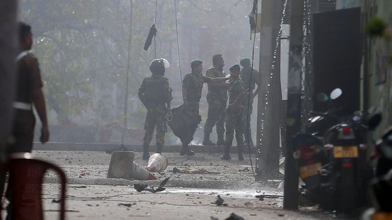 Bomb squad officers at the site of an exploded van in Colombo, Sri Lanka