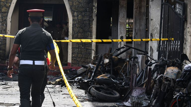 Sri Lankan security personnel walk past debris outside Zion Church following an explosion in Batticaloa in eastern Sri Lanka on April 21, 2019. - A series of eight devastating bomb blasts ripped through high-end hotels and churches holding Easter services in Sri Lanka on April 21, killing nearly 160 people, including dozens of foreigners