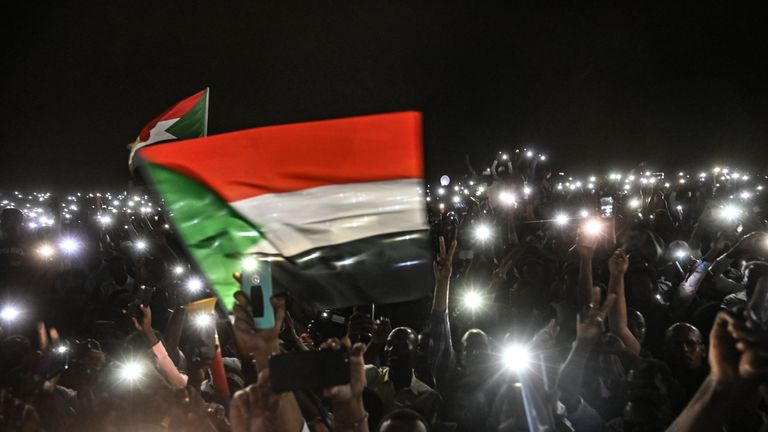 Sudanese protesters open their smartphones lights during a protest outside the army headquarters in the capital Khartoum on April 21, 2019
