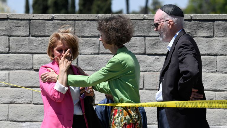 Synagogue members console one another outside of the Chabad of Poway Synagogue