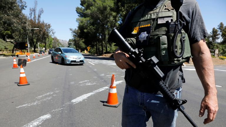 A police officer secures the area following a shooting at a synagogue in Poway
