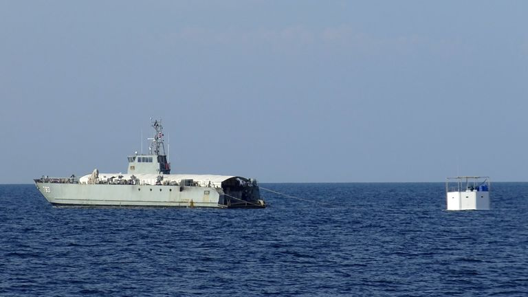 A Royal Thai navy ship drags a floating home off Phuket Island
