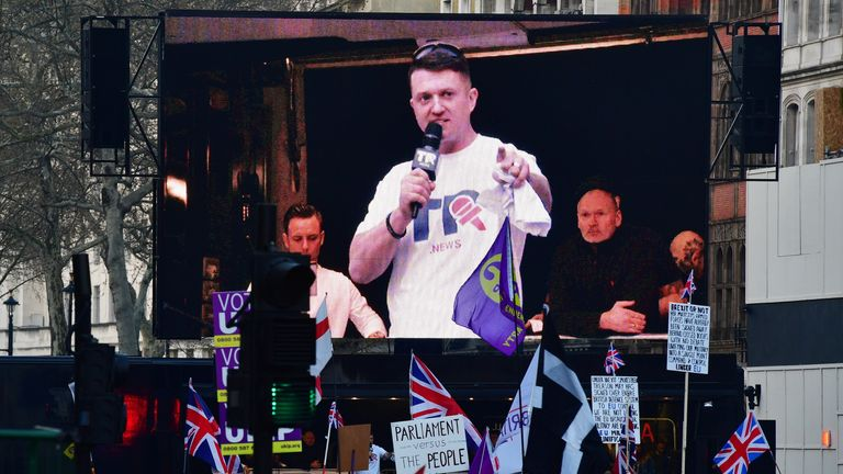 Robinson appears on a screen at pro-Brexit protests on 29 March