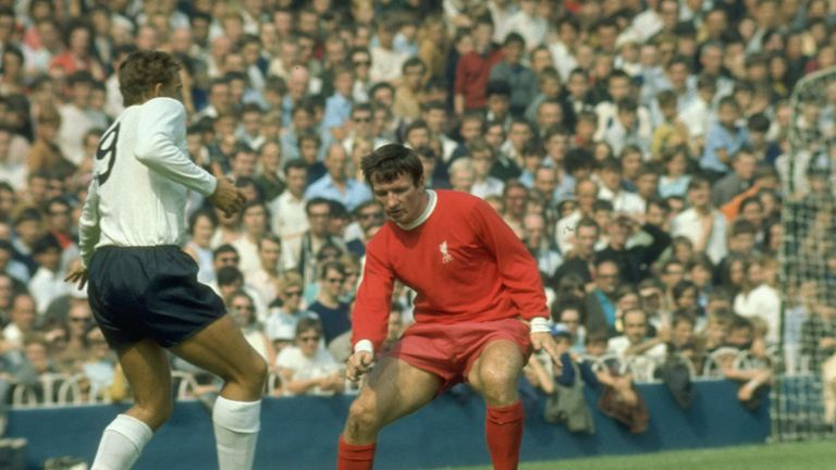Smith (R) takes Martin Chivers of Tottenham Hotspur at Anfield