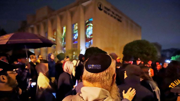 A group gathers outside the Tree of Life Synagogue for a vigil to honor the victims of the Saturday attack