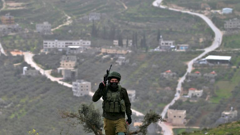 An Israeli soldier keeps position during clashes with Palestinian protesters following a demonstration against Jewish settlements in the West Bank village of Urif, south of Nablus, on February 15, 2019