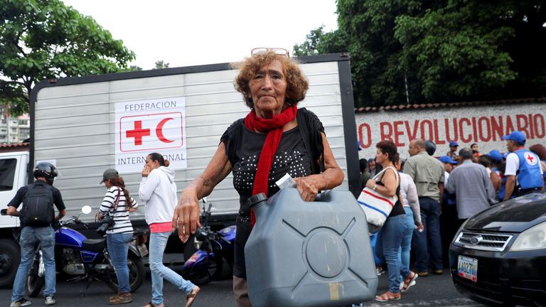 A woman carried a water container in Caracas