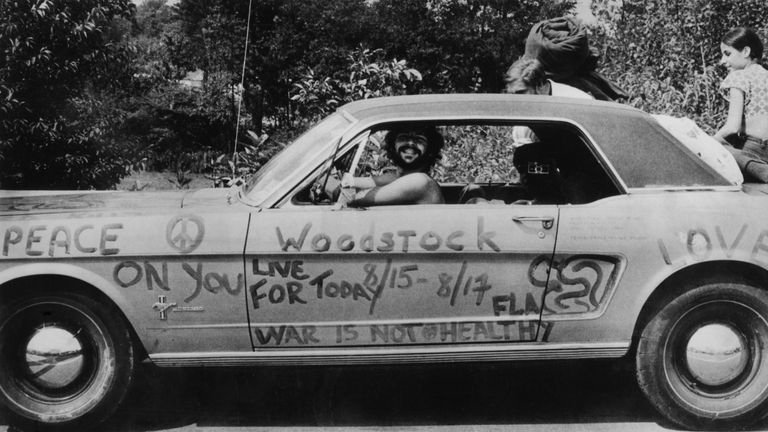 A music fan at Woodstock pop festival in his car covered in anti-war slogans for love and peace. (Photo by Three Lions/Getty Images)