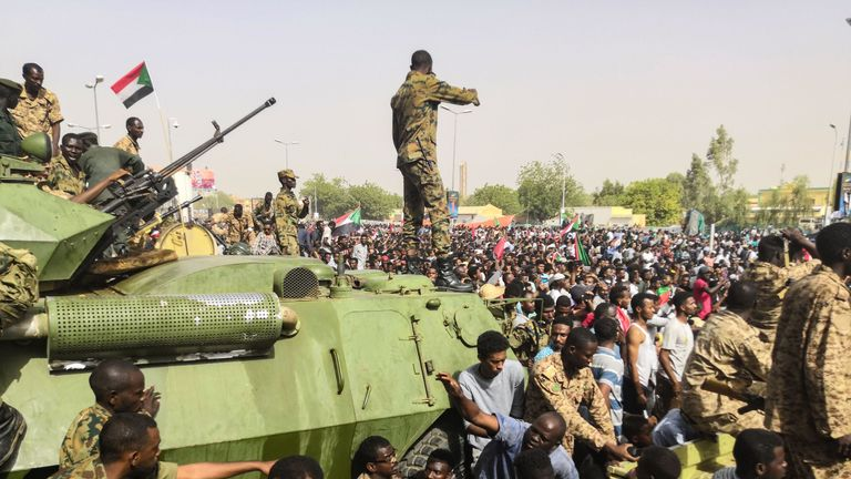 Sudanese soldiers stand guard on armoured military vehicles in the capital Khartoum