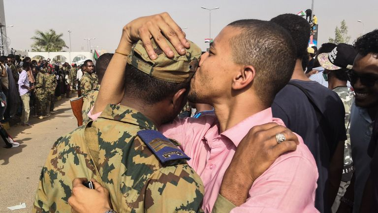 A Sudanese anti-regime protester kisses a soldier on the head