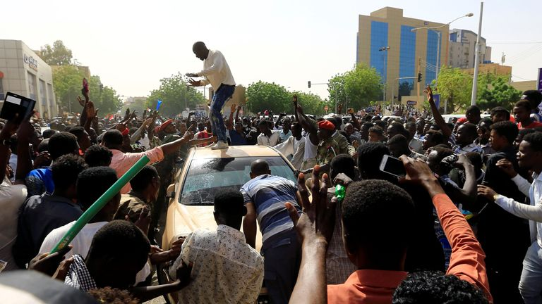 Sudanese demonstrators block the vehicle of a military officer in protest against the army's announcment