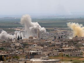 Smoke rises above buildings during shelling by Syrian regime forces and their allies on the town of Khan Sheikhun in the southern countryside of the rebel-held Idlib province on May 11, 2019