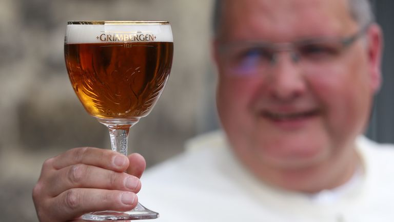 Norbertine Father Karel poses with a Grimbergen beer, symbolised by a phoenix, in the courtyard of the Belgian Abbey of Grimbergen before announcing that the monks will return to brewing after a break of two centuries, in Grimbergen, Belgium May 21, 2019.  REUTERS/Yves Herman