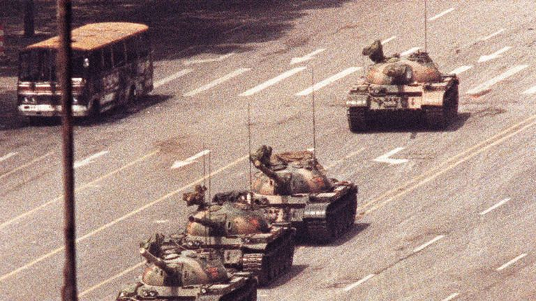 A man stands in front of a convoy of tanks in the Avenue of Eternal