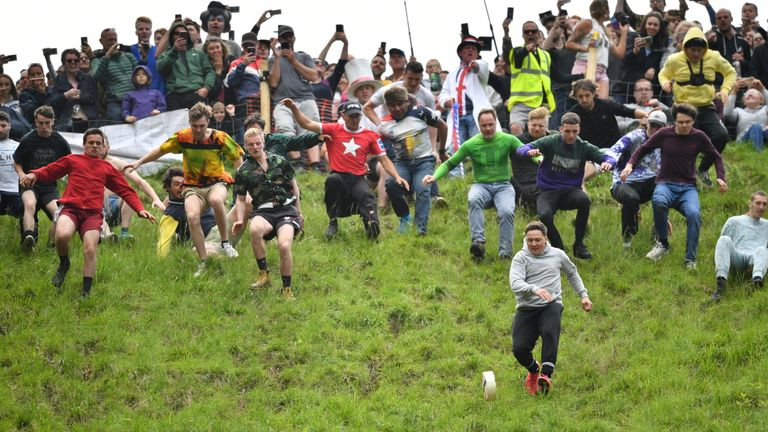 Daredevils chase cheese down a hill in Gloucester