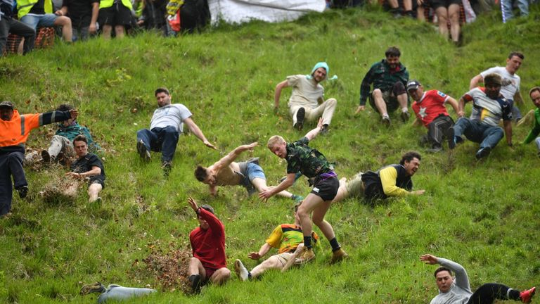 Participants take part in the annual cheese rolling competition at Cooper's Hill in Brockworth, Gloucestershire.