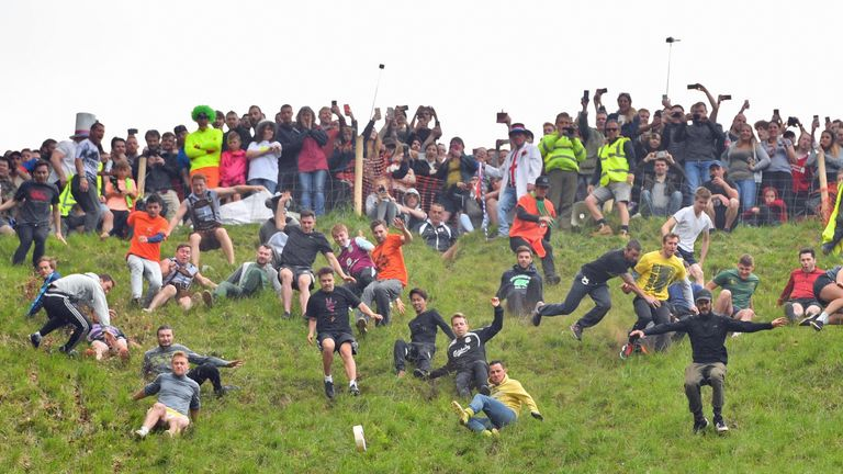 Participants take part in the third men's downhill race during the annual cheese rolling competition at Cooper's Hill in Brockworth, Gloucestershire.