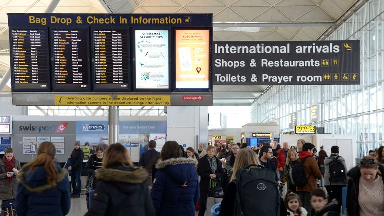 People view the check in information board at London Stansted Airport.